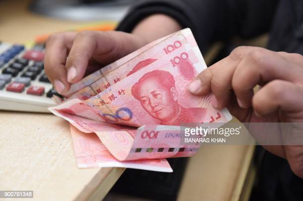A Pakistani currency dealer counts Chinese currency for his customer at his shop in Quetta on January 3 2018 Pakistan will allow the Chinese yuan to...