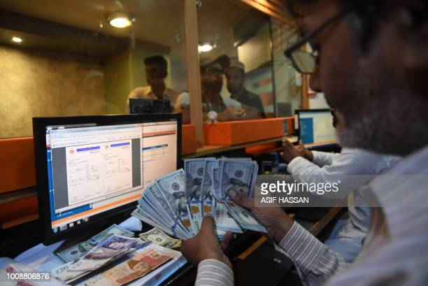 A Pakistani currency dealer counts USD banknotes at a currency exchange shop in Karachi on August 1 2018 Pakistan's next government faces growing...