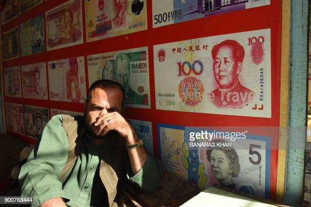 A Pakistani currency dealer waits for the customer in Quetta on January 3 2018 Pakistan will allow the Chinese yuan to be used for imports exports...