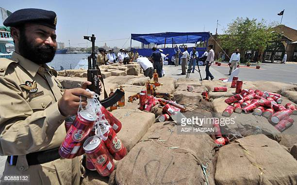 A Pakistani Custom official display cans of beer retieved from a cache of seized liquor for media representatives in Karachi on April 28 2008...