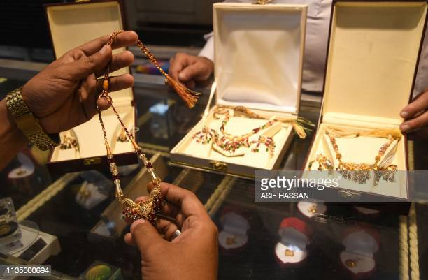 A Pakistani customer checks gold jewellery at a shop in Karachi on April 5 2019 Pakistan will continue to face macroeconomic challenges despite tight...