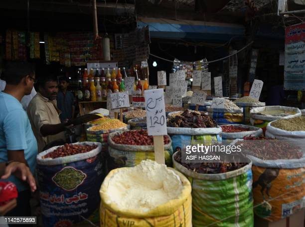 Pakistani customers buy grocery items at a market in Karachi on May 10 2019 Pakistan's growth rate is set to hit an eightyear low a government report...