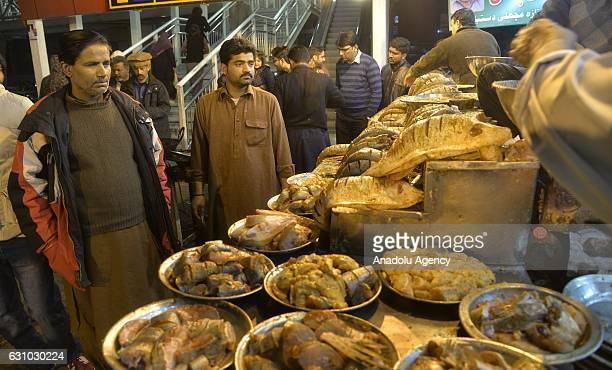 Pakistani customers look at the spicy liced fish at a shop following a significiant increase in the demand of fish due to a longawaited winter rain...
