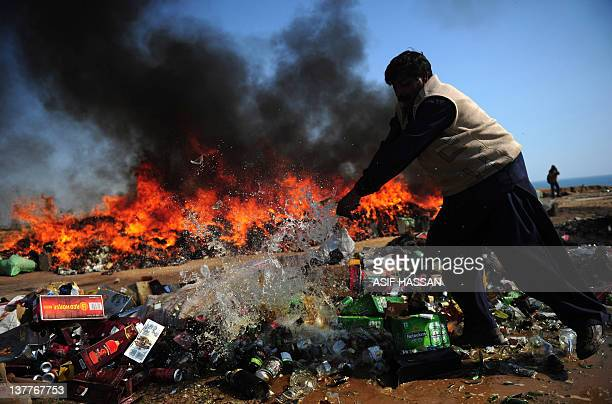 A Pakistani customs official breaks liquor bottles as seized heroin and hashish burn in the outskirt of Karachi on January 26 2012 The customs...