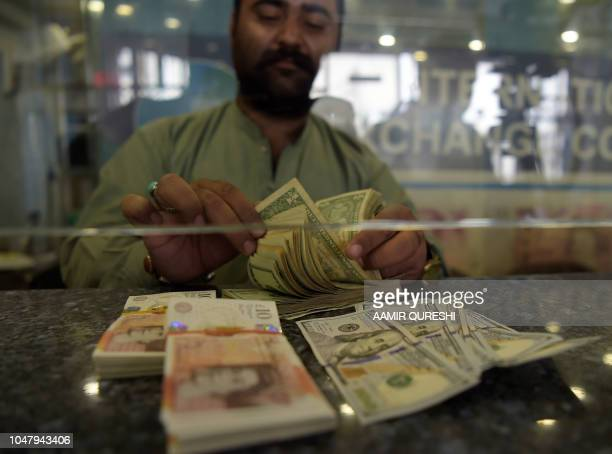 A Pakistani dealer counts US dollars at a currency exchange shop in Islamabad on October 9 2018 The International Monetary Fund said October 9...