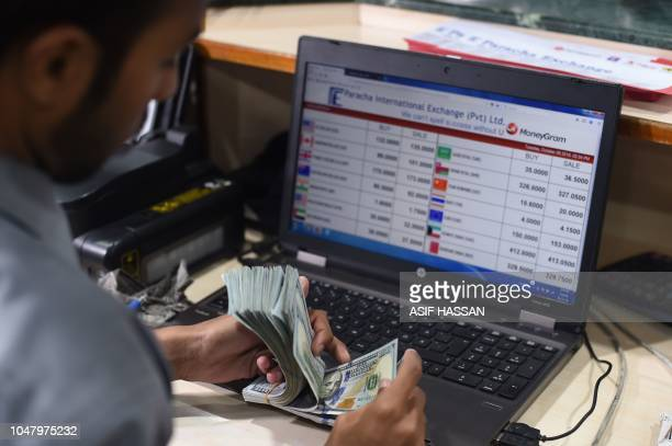 A Pakistani dealer counts US dollars at a currency exchange shop in Karachi on October 9 2018 The International Monetary Fund said October 9 Pakistan...