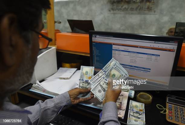 A Pakistani dealer counts US dollars at a currency exchange shop in Karachi on November 30 2018 Pakistan's rupee plunged almost five percent to a...