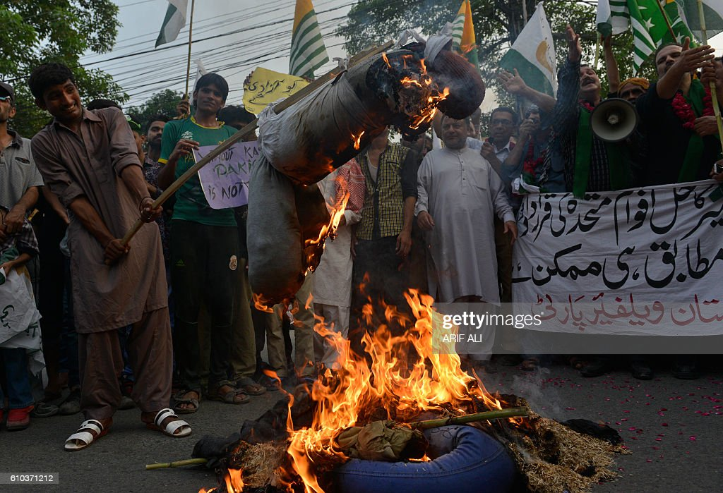 Pakistani demonstrators burn effigies of Indian Prime Minister Narendra Modi and Foreign Minister Sushma Swaraj during a protest to show solidarity...