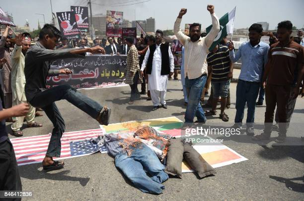 Pakistani demonstrators burn effigies of Myanmar leader Aung San Suu Kyi and Indian Prime Minister Narendra Modi during a protest against the Myanmar...