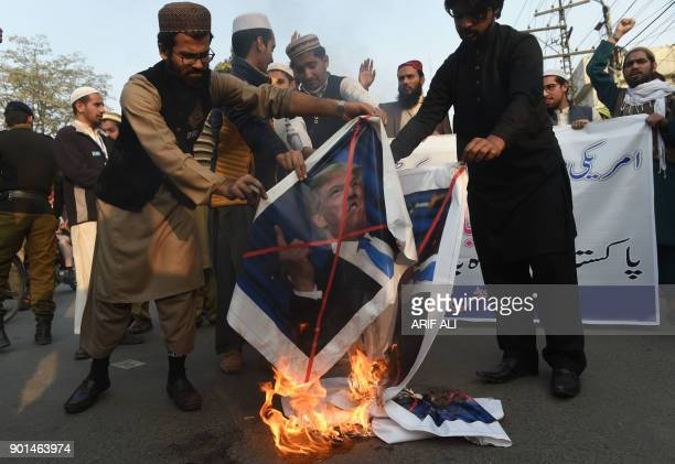 Pakistani demonstrators burn images of US President Donald Trump and the US flag during a protest against US aid cuts in Lahore on January 5 2018 The...