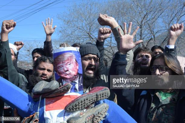 Pakistani demonstrators hold an effigy of US President Donald Trump and India Prime Minister Narendra Modi as they shout slogans during a protest...