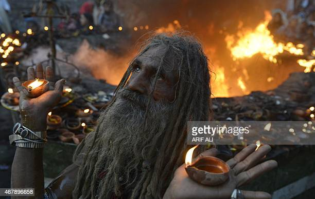 A Pakistani devotee carries light lamp as he stand infront of fire at the shrine of Sufi saint Hazrat Shah Hussain popularly known as Madhu Lal...