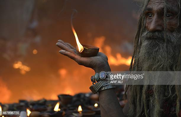 A Pakistani devotee carries light lamp as he stands in front of a fire at the shrine of Sufi saint Hazrat Shah Hussain popularly known as Madhu Lal...