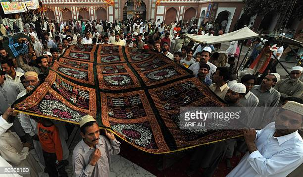 Pakistani devotees carry a 'chaddar' for the grave of the Sufi saint Mian Mir Sahib during his 364th death anniversary at a shrine in Lahore on March...