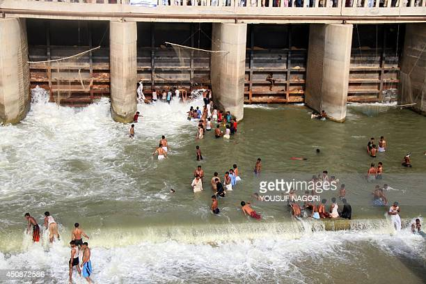 Pakistani devotees cool themselves in water basins on June 18 2014 at the shrine of 13th century Muslim Sufi saint Lal Shahbaz Qalandar in Sehwan 250...