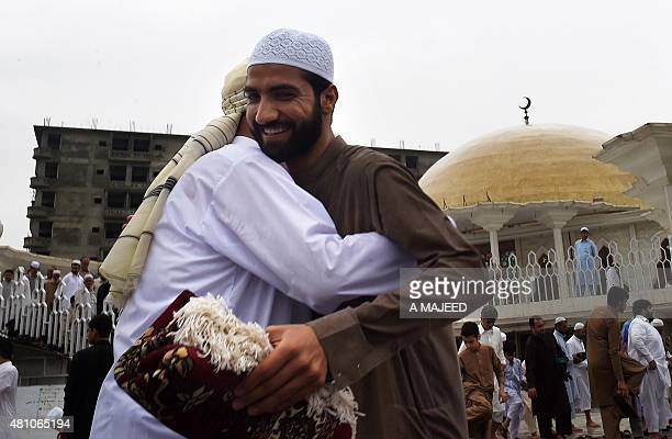 Pakistani devotees embrace after offering prayers on the last Friday of Ramadan ahead of the Eid alFitr holiday in Peshawar on July 17 2015 Millions...