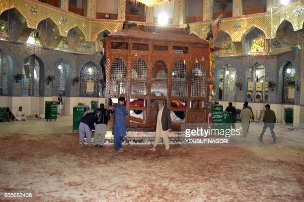 Pakistani devotees look at the bloodstained floor of the shrine of 13th century Muslim Sufi Saint Lal Shahbaz Qalandar after a bomb explosion in the...