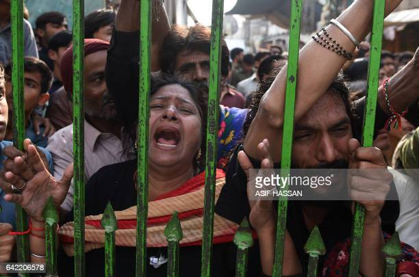 Pakistani devotees react as they gather outside closed gate of the shrine of 13th century Muslim Sufi saint Lal Shahbaz Qalandar a day after a bomb...