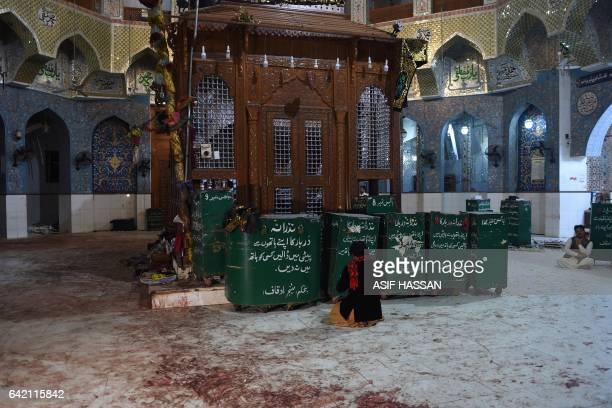 A Pakistani devotees sits on the bloodstained floor a day after a bomb attack hit the 13th century Muslim Sufi shrine of Lal Shahbaz Qalandar in the...