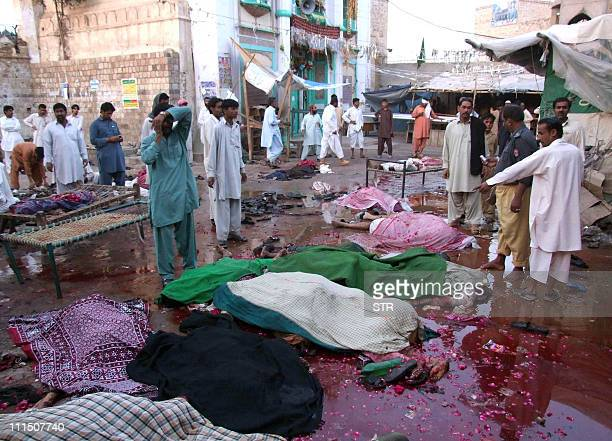 Pakistani devotees stand among the blast victims bodies following a suicide bomb attacks outside the shrine of 13th century Sufi saint Ahmed Sultan...