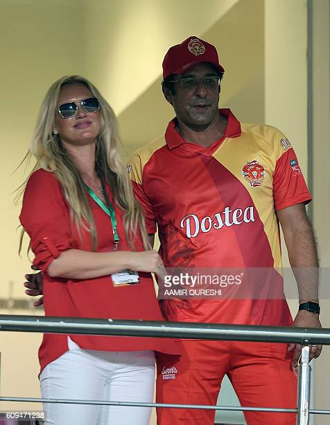 Pakistani director and bowling coach of Islamabad United Wasim Akram watches the match with his wife Shaniera Akram during an exhibition match at...