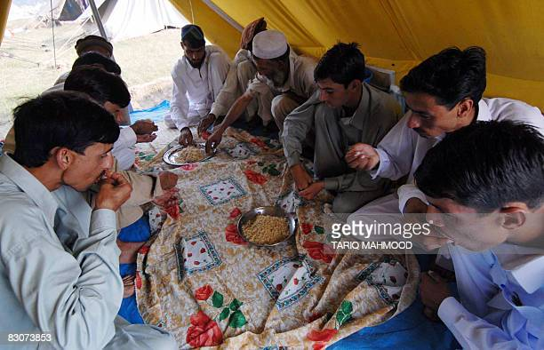 Pakistani displaced people from the troubled district of Bajaur eat at a makeshift camp in Mardan on October 1 on the first day of their religious...