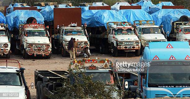 Pakistani drivers stand next to their trucks loaded with food and military vehicles for NATO and USled forces in Afghanistan parked in Peshawar on...