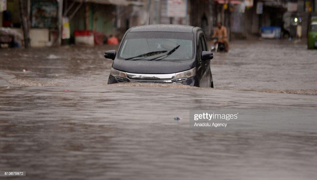 Pakistani drives a car through a flooded street after heavy monsoon rains hit Rawalpindi province of Pakistan on July 13 2017 Heavy monsoon rains...