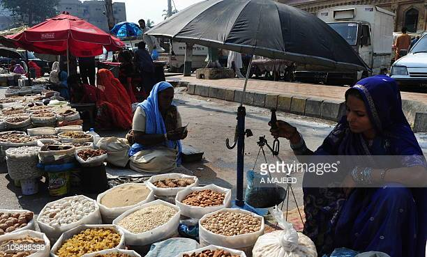 Pakistani dry fruit vendors wait for customers on a roadside in Karachi on March 5 2011 Pakistan said it would increase petrol prices by about five...