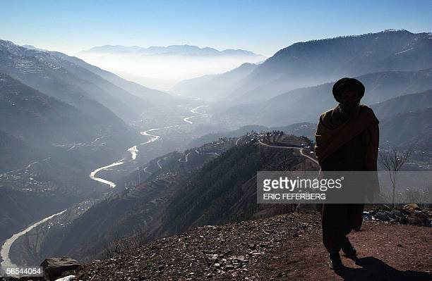 Pakistani earthquake survivor walks on a path overlooking the Pakistani Kashmiri city of Balakot 09 January 2006 two days ahead of the Muslim...