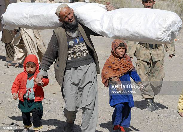 A Pakistani earthquake survivor walks with his children as he carries a tent distributed by the army at a hilly area of Killy Kach one of about eight...