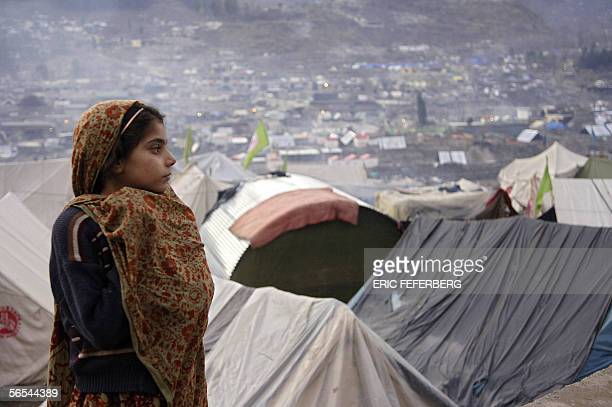 Pakistani earthquake survivor watches over the Pakistani Kashmiri city of Balakot as she stands outside her tent at a camp for people made homeless...