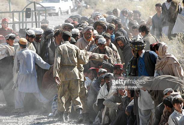 Pakistani earthquake survivors lineup as they wait for relief supplies at a hilly area of Wam one of about eight sparsely populated villages...