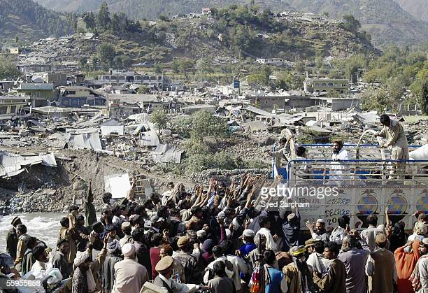 Pakistani earthquake victims receive relief goods after troops cut through landslides to get aid to tens of thousands of villagers in two Kashmir...