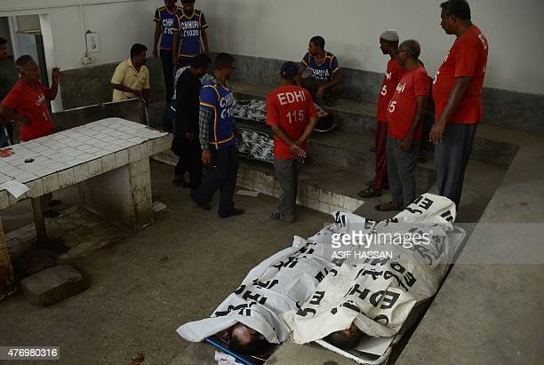 Pakistani Edhi Foundation volunteers gather near the bodies of suspected militants killed in an exchange of fire with police at a morgue in Karachi...