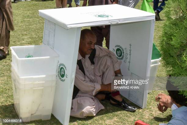 A Pakistani election official sits under voting materials as he waits for transport at a distribution centre in Quetta on July 24 2018 Pakistan will...