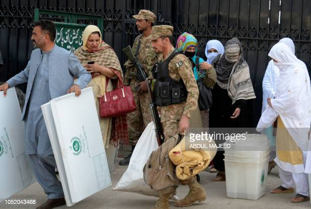 Pakistani election presiding officers carry election materials for a byelection after receiving them from a distributing point in Peshawar on October...