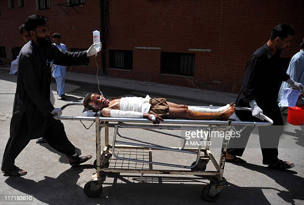 Pakistani emergency and rescue personnel transport an injured boy after a bomb blast at a bus terminal near a market in Matani about 20 kilometres...