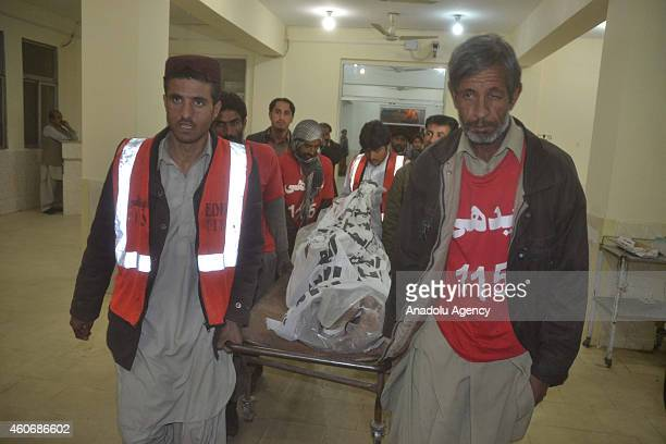 Pakistani emergency workers carry a body of TehrikiTaliban Pakistan militant in a hospital in Quetta Pakistan on December 19 2014 Pakistani security...