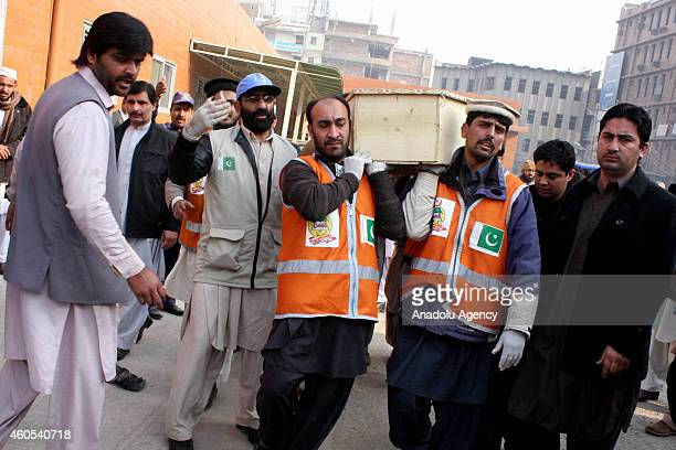 Pakistani emergency workers carry the coffin of a Taliban attack victim in the northwestern Pakistani city of Peshawar on December 162014 Taliban...