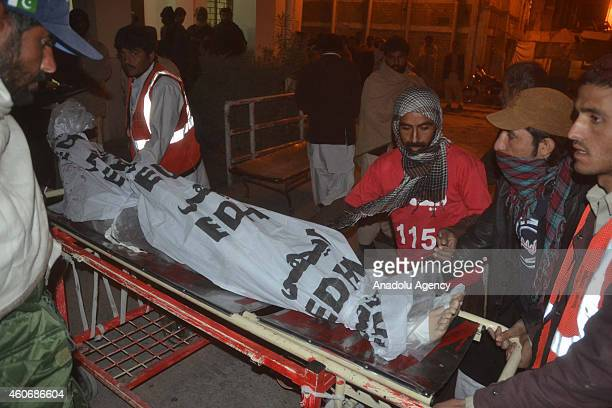 Pakistani emergency workers shift a body of TehrikiTaliban Pakistan militant from an ambulance to a hospital in Quetta Pakistan on December 19 2014...