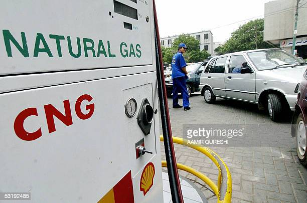 Pakistani employee of a service station helps drivers to form a queue to fill their vehicles with Compressed Natural Gas in Karachi 04 July 2005...