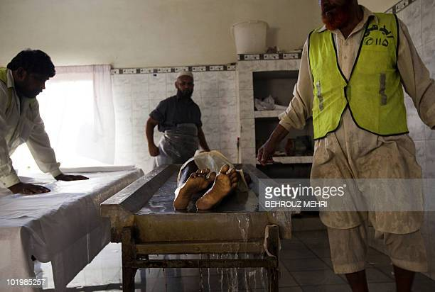 Pakistani employees wash a body of an elderly man to prepare him for a burial ceremony at The Edhi Morgue in Karachi on February 20 2010 The Edhi...