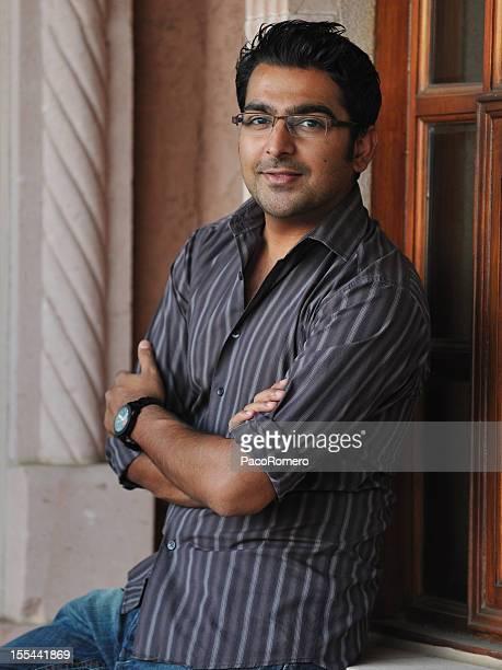 pakistaní empresario sentado al aire libre con brazos cruzados - handsome pakistani men fotografías e imágenes de stock