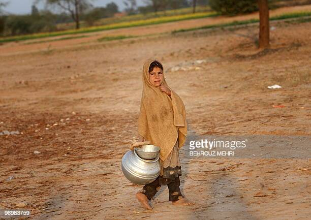 A Pakistani ethnic Pashtun girl takes a milk jar outside her makeshift house in the town of Khewra some 200 kms south of the capital Islamabad on...