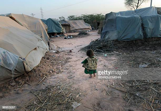 A Pakistani ethnic Pashtun girl walks towards her makeshift tent in the town of Khewra some 200 kms south of the capital Islamabad on February 14...