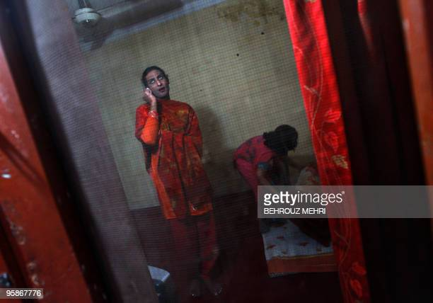 Pakistani eunuch Sana speaks on her mobile as her eunuch room mate Kiren adjusts the bed in their room in Rawalpindi on January 18 2010 AFP...