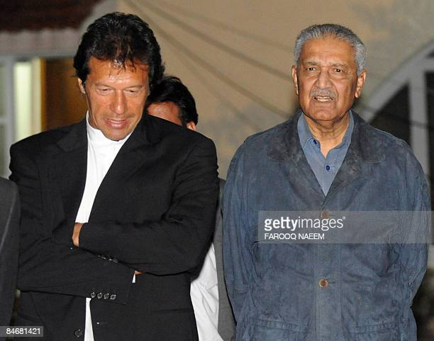 Pakistani excricket star turned politician Imran Khan walks with disgraced nuclear scientist Abdul Qadeer Khan after a meeting at his residence in...
