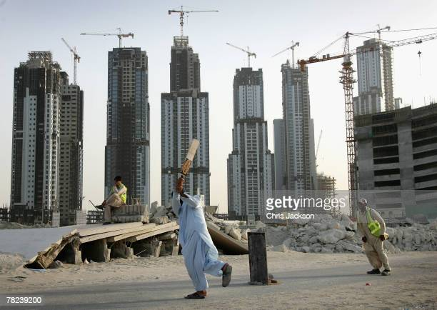 Pakistani expatriot construction workers play cricket during a break from labouring on a construction site on December 3 2007 in Dubai United Arab...
