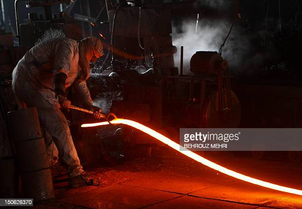 A Pakistani factory worker handles a molten steel rod at a steel mill in Islamabad on January 15 2010 Electricity and gas shortages in recent years...